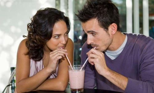 homem e mulher se olhando e dividindo milk shake