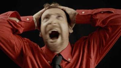 homem de roupa social vermelha gritando com a mão na cabeça